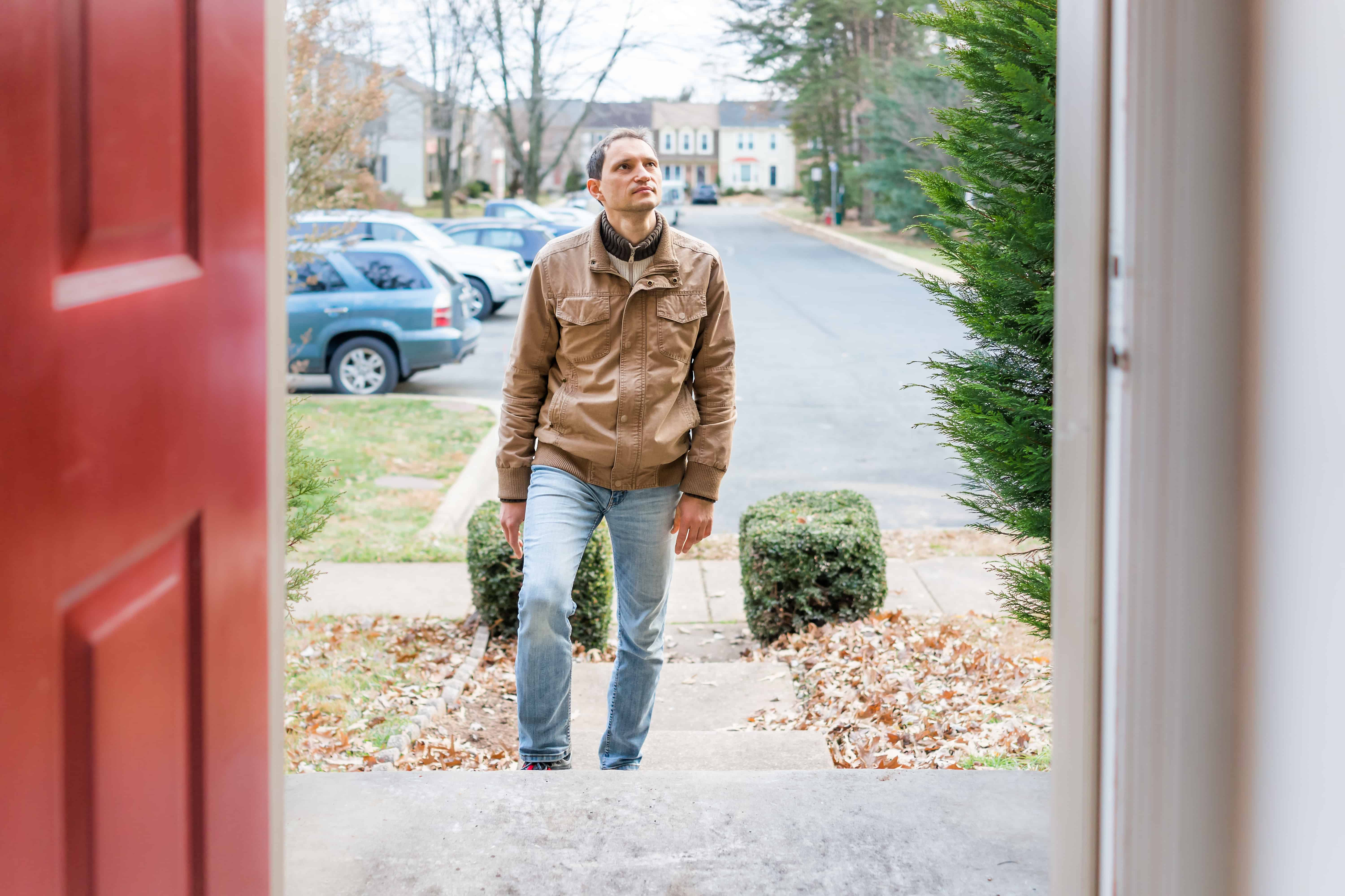 Young man standing on the front steps in front of house looking to buy real estate residential neighborhood